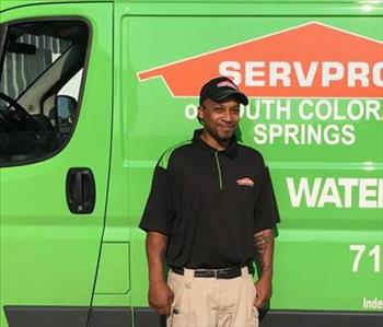 Male employee smiling in front of a green van