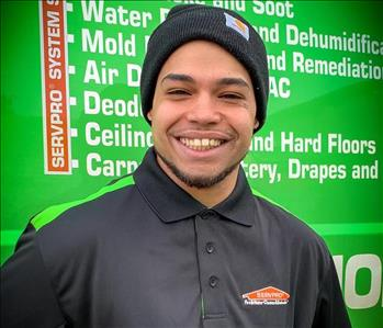 Male employee smiling in front of a green background