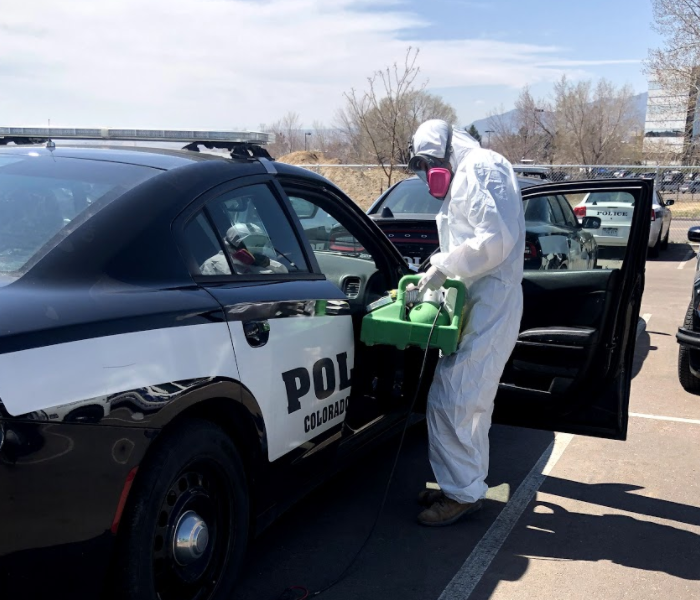 a guy in a white suit with green equipment near a police car